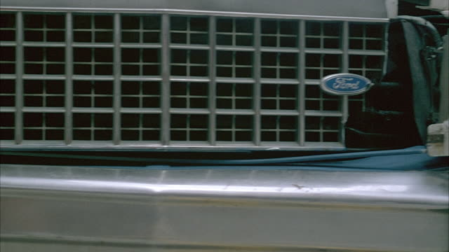 CLOSE ANGLE OF RADIATOR GRILLE AND SMASHED RIGHT HEADLIGHTS ON 1980'S BLUE FORD CROWN VICTORIA. PANS LEFT ALONG RADIATOR GRILLE TO SIDE OF CAR