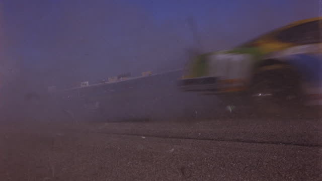 WIDE ANGLE OF STOCK RACE CAR ON SIDE OF RACETRACK. CAR'S ENGINE BEGINS TO SMOKE AND THEN SPEEDING CARS CRASH INTO IT. CAR PARTS SCATTER ON RACE TRACK WHILE RACE CARS SLOW TO STOP. COULD BE NASCAR.