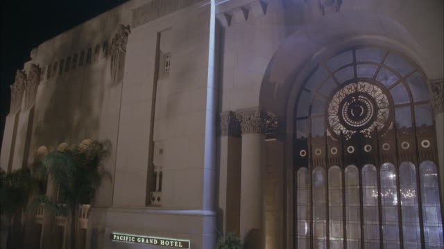 PAN DOWN OF FRONT ENTRANCE AND FACADE OF PARK PLAZA HOTEL  SIGN READS PACIFIC GRAND HOTEL. CAMERA PANS DOWN TO RED CARPET AND CROWD. BANNER OVER DOORS READS WELCOME BRIDGEPORT HIGH SENIOR PROM.