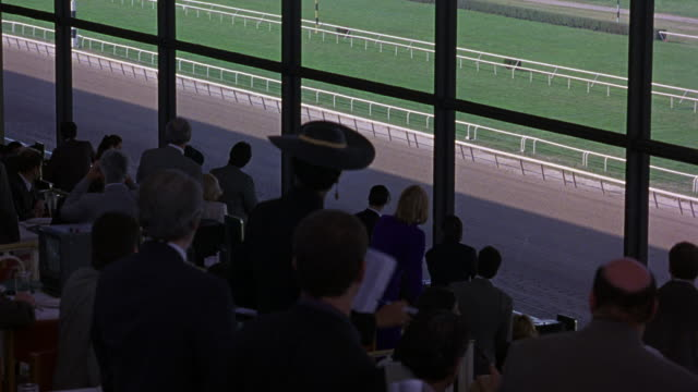 medium angle of spectators watching horse race at belmont park race track from indoor stadium, looks like upper class seating area. see spectators cheer as horses run around track counterclockwise. - racehorse stock videos & royalty-free footage