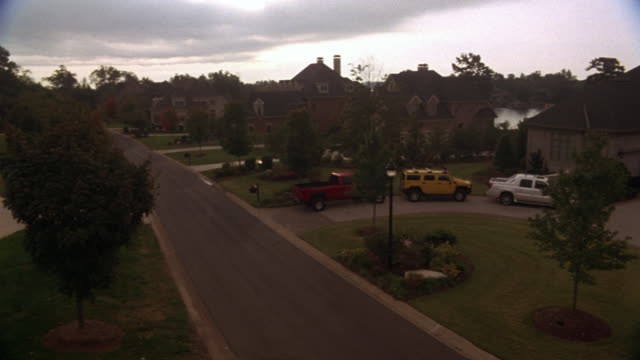 high angle down shows upper class neighborhood with mansions along street. pan right to show mansion with various vehicles including motorboat, hummer, - upper class stock videos & royalty-free footage