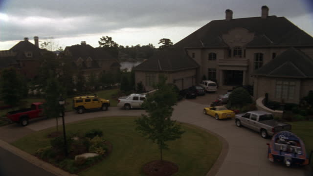 pan left to right shows upper class neighborhood with mansions along street then focuses on two story mansion with various vehicles including motorboat, hummer - upper class stock videos & royalty-free footage