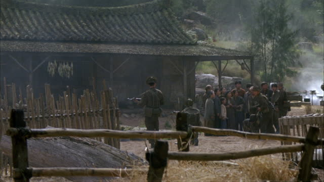medium angle of small north korea peasant village. see peasants gathered in front of house. see smoke rising from a pit. see hay hanging from bamboo pole fence in foreground. - korea stock videos & royalty-free footage