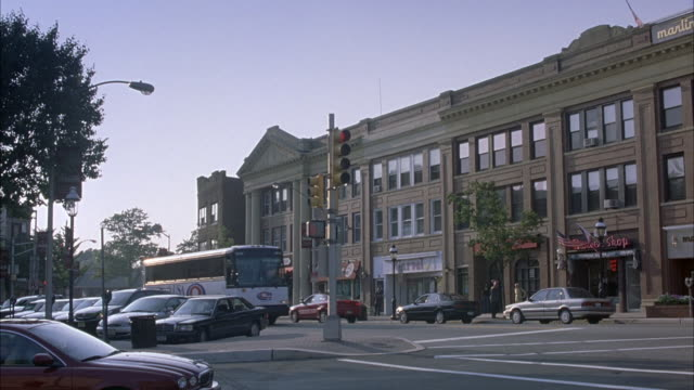wide angle of office building or shopping center with stores on bottom level. see passing traffic in foreground. see white coach usa bus stopped at light. - https点の映像素材/bロール