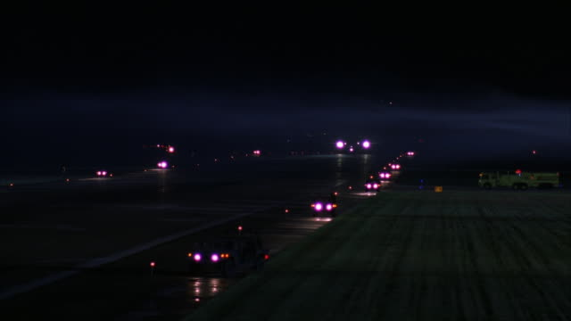 medium angle of air force one jet driving down runway immediately followed by several emergency vehicles with lights and sirens on. - air force one stock videos & royalty-free footage