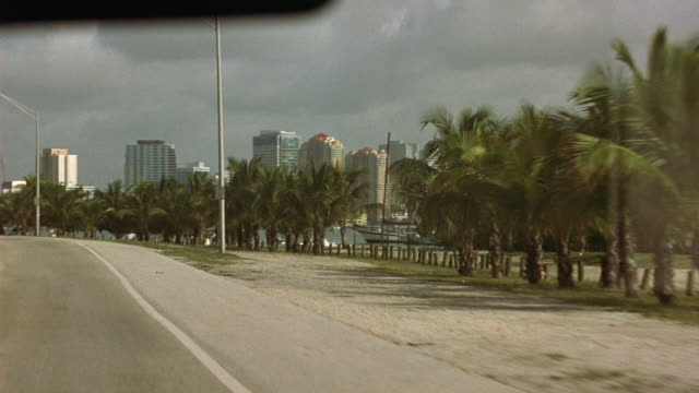 vidéos et rushes de driving pov from passenger side of moving vehicle. six lane road with trees and palms in the median. see miami skyline in background. pans right and see a bay with docked boats. - miami