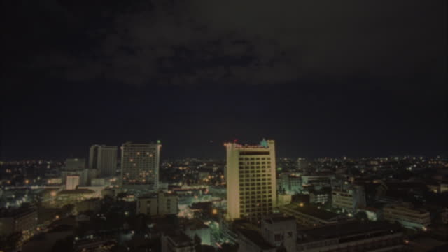 WIDE ANGLE SHOT OF ASIAN CITY SKYLINE. SEE THREE TALL BUILDINGS OR SKYSCRAPERS, ONE OF WHICH IS POSSIBLY ROYAL LANNA TOWER.