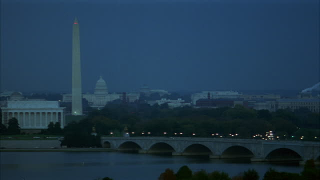 wide angle of washington monument on left and arlington memorial bridge on right over reflecting pool. washington dc skyline in far background. overcast. - reflecting pool washington dc stock videos & royalty-free footage