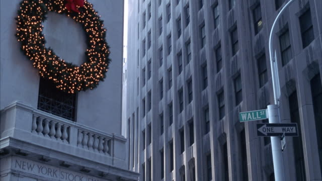 PAN DOWN FROM CHRISTMAS WREATH WITH LIGHTS ABOVE ENGRAVING THAT READS NEW YORK STOCK EXCHANGE AND SIGNS THAT READ WALL ST. AND ONE WAY TO ENTRANCE OF BUILDING AND PEDESTRIANS WALKING BY.