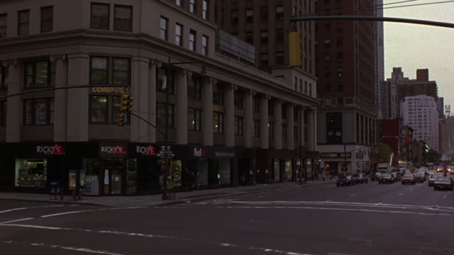 medium angle of four lane new york city street. looks like 8th avenue and west 58th street intersection. see traffic moving right to left. see ricky's storefront on street corner of intersection. see pedestrians crossing street. - anno 1999 video stock e b–roll