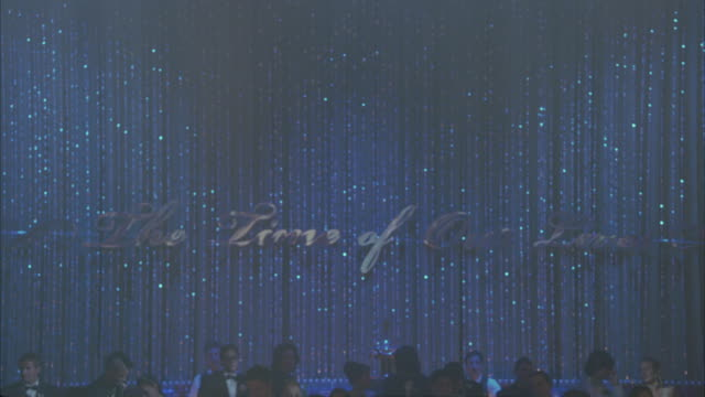 pan up from sign: the time of our lives on beaded and sparkly curtain. heads of high school students in evening gowns and tuxedos standing in front of stage. end on spotlights. could be school prom, dance, party, celebration or performance. - beaded curtain stock videos & royalty-free footage