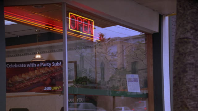 medium angle of subway sandwich restaurant storefront.  see neon red, yellow, and orange open sign.  see celebrate with a party sub! poster on the glass window. - sandwich stock videos & royalty-free footage