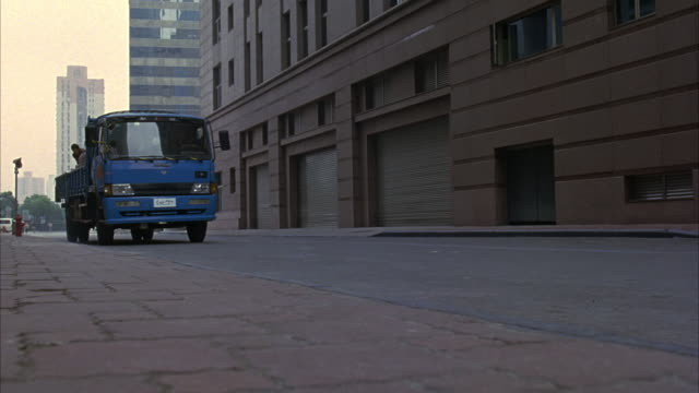 WIDE ANGLE OF STREETS OR ALLEYS IN FUTURISTIC DOWNTOWN AREA. SEE HIGH RISE BUILDINGS IN BACKGROUND. SEE BLUE NEWSPAPER DELIVERY TRUCK DRIVE TOWARDS RIGHT OF CAMERA.