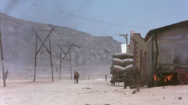 medium angle of dusty road of deserted western town. see wagon loaded with barrels parked alongside of warehouse or building. see mountains in the background behind row of old-fashioned telephone poles. - 1914年点の映像素材/bロール