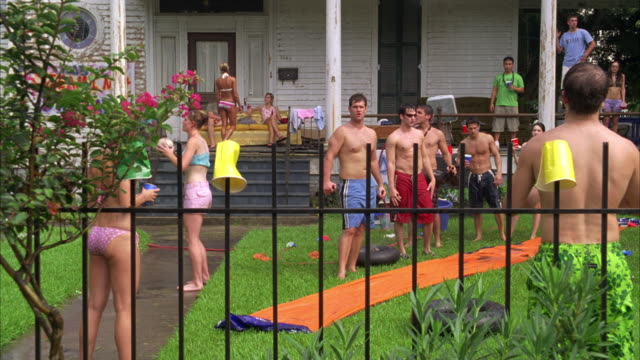 hand held of college students outside fraternity or frat house wearing bathing suits, drinking beer. a sign reads never to hot to party tt05.  drinking on college campus. a large two story house or mansion. slip and slide. - louisiana stock videos & royalty-free footage
