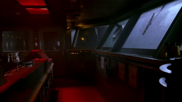 medium angle ship's bridge control room. see control panel, door beyond, and windows opposite panel along right. heavy rain hits windows and windshield wipers move back and forth. could be storm. - schiff stock-videos und b-roll-filmmaterial