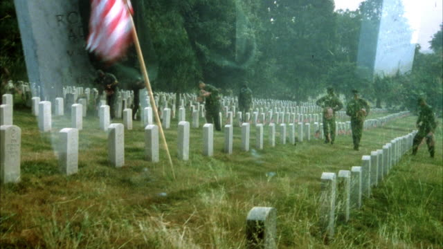 MEDIUM ANGLE OF SOLDIERS PLACING AMERICAN FLAGS IN FRONT OF HEADSTONES AT CEMETERY, POSSIBLY ARLINGTON NATIONAL CEMETERY. PROBABLY BEFORE MEMORIAL DAY. SUPERIMPOSED CLOSER IMAGE OF SOLDIERS PLACING FLAGS IN FRONT OF HEADSTONES.