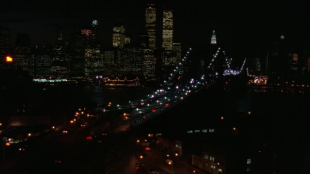 wide angle of brooklyn bridge with new york city skyline in background. see cars on bridge. see world trade center twin towers. pans left to show more city and freeways. neg cut. - 1995年点の映像素材/bロール