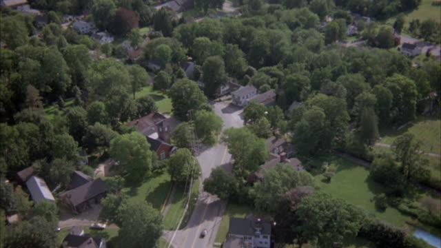 HIGH-LEVEL AERIAL OF SMALL NEW ENGLAND TOWN FOLLOWING A TOWN STREET TOWARDS THE TOP OF THE SHOT. STREET VEERS LEFT AND SHOT MOVES WITH THE STREET KEEPING THE STREET IN THE CENTER OF THE SHOT.