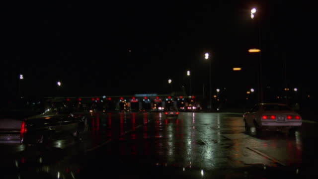 MEDIUM ANGLE POV DRIVER IN CAR OF DRIVING DOWN HIGHWAY. POV APPROACHES TOLLBOOTH PLAZA WITH POLICE CARS PARKED ACROSS HIGHWAY TO FUNNEL TRAFFIC DOWN TO ONE LANE. SEE POLICE STANDING OUTSIDE POLICE CARS WITH BIZBAR LIGHTS FLASHING.