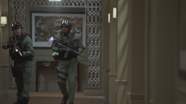 vidéos et rushes de medium angle of hallway in upper class hotel and police officers armed with guns.  swat team in uniforms with sheriff printed on back kick in door. crime scene. - stéréotype de la classe supérieure