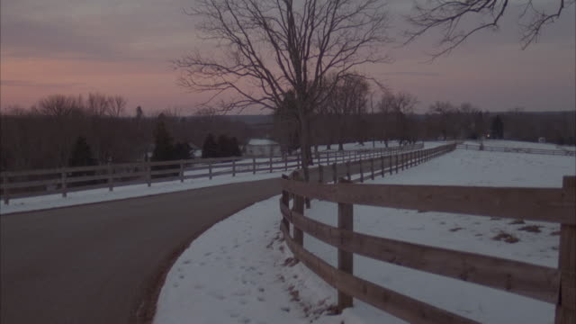 tracking shot of green ford explorer driving along country road with snow. pans left past wood fence through trees to mansion on left. - ford motor company stock videos and b-roll footage
