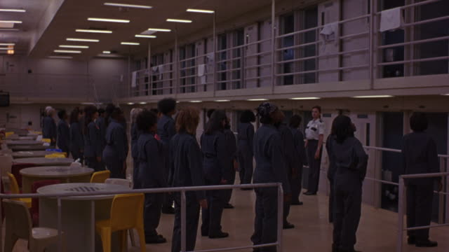 vidéos et rushes de medium angle of correctional officer or prison guard leading a group of women prisoners  in physical exercises. see all women start to do jumping jacks. - prison
