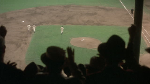 HIGH ANGLE DOWN OF BASEBALL FIELD. POV FROM BLEACHERS, BEHIND SPECTATORS. SEE SPECTATORS STANDING, START TO CLAP ONCE BASEBALL TEAM RUNS ONTO FIELD.