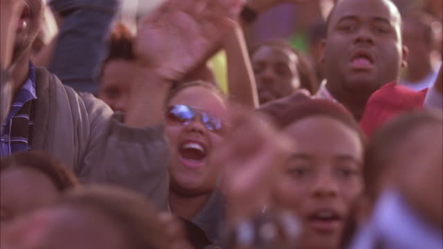 vídeos de stock e filmes b-roll de medium angle of crowd of men, women, students watching event offscreen. reactions, smiling, applause. rhythmic crowd motion. could be concert audience at university, college. - geórgia sul dos estados unidos