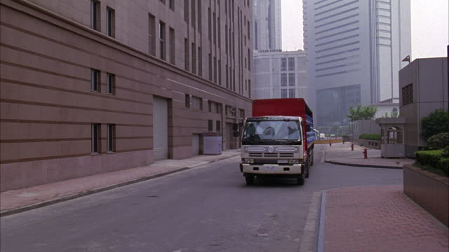 MEDIUM ANGLE OF SMALL ALLEY OR STREET. SEE HIGH RISE BUILDINGS IN BACKGROUND. SEE RED TRUCK WITH 5 GALLON WATER CONTAINERS DRIVE TOWARDS CAMERA.