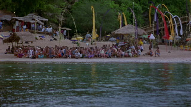 wide angle of village on beach. large group of people sitting together on beach in large circle. could be ceremony. - thatched roof stock videos & royalty-free footage