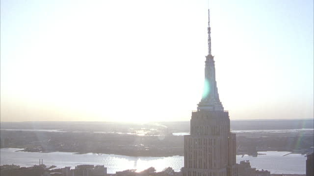 vidéos et rushes de aerial pull back of empire state building. pov starts with close up of top of building and pulls back while circling building. see sun low in sky to west. - world trade center manhattan