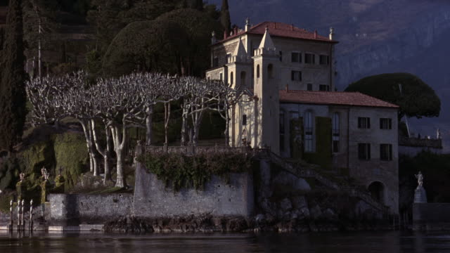 medium angle of multi-story, split-level, upper-class, renaissance, 15th to 17th century villa or castle on waterfront. see staircase leading down to boat dock in foreground. - sardinien stock-videos und b-roll-filmmaterial