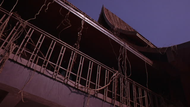 up angle of two story building balcony with railing and dried vines, steeple style roof. stunt man rolls over railing, falls. could be asian temple. - zweistöckiges bauwerk stock-videos und b-roll-filmmaterial