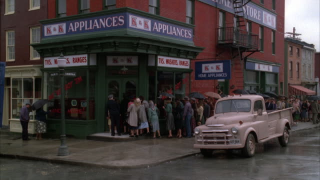 WIDE ANGLE OF STREET CORNER WITH GREEN APPLIANCE STOREFRONT, POSSIBLY LOWER LEVEL OF RED BRICK APARTMENT BUILDING. PEOPLE ARE LINED UP FROM STORE ENTRANCE TO MIDDLE OF BLOCK.