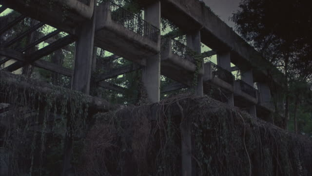 UP ANGLE OF VINE-COVERED MULTI-STORY BUILDING ATRIUM. MAN AND WOMAN ON MOTORCYCLE FLY INTO FRAME AND LAND IN HEDGES. MOSS COVER FALLS, REVEALING CARDBOARD BOXES USED AS CUSHION IN STUNT.