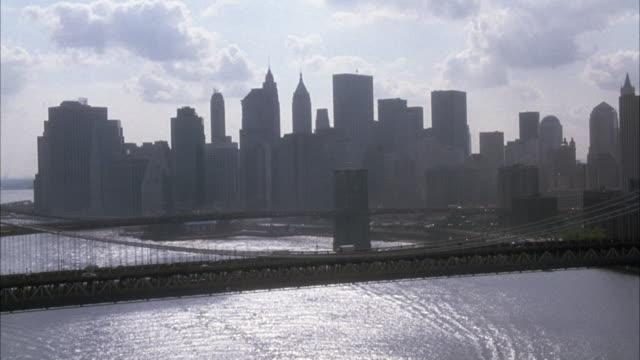 AERIAL POV MOVING SOUTH TOWARDS LOWER MANHATTAN NEW YORK CITY SKYLINE OVER EAST RIVER. POV PASSES OVER MANHATTAN BRIDGE AND BROOKLYN BRIDGE BELOW.