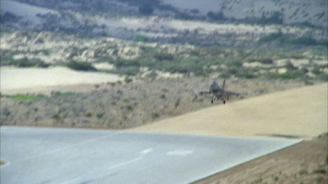 TRACKING SHOT OF A CAMOUFLAGE F-16 FIGHTER JET APPROACHING RUNWAY IN DESERT. SEE JET BEGIN TO TOUCH DOWN. SEE TENTS ON SIDE OF RUNWAY. MIDDLE EAST.