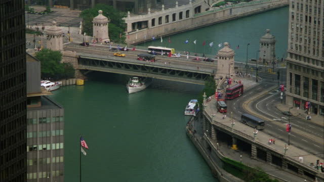 high angle down on michigan avenue bridge over the chicago river. see white passenger or tourist ferry or boat pass under bridge and into center of shot. see light traffic on city streets. camera pulls back at end of shot. - michigan avenue bridge stock videos and b-roll footage