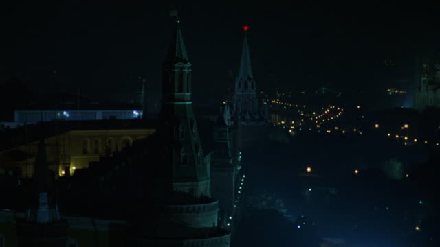 medium angle pan left of city skyline of moscow at night. see street lamps and lights and spires. pans left to red square with st. basil's cathedral in left background. - cathedral stock videos & royalty-free footage