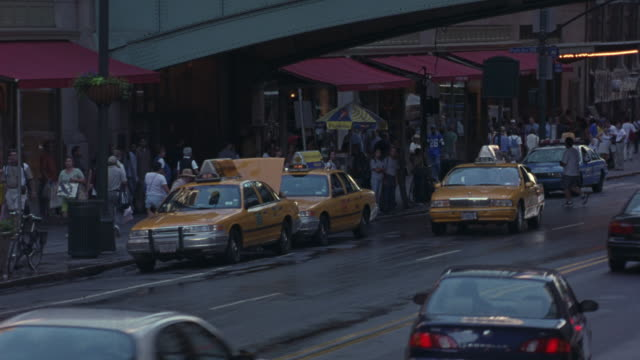 medium angle of crowded new york city street. see yellow taxi cabs lined up along side of street. see crowds of people along sidewalk. - 2000 stock videos & royalty-free footage
