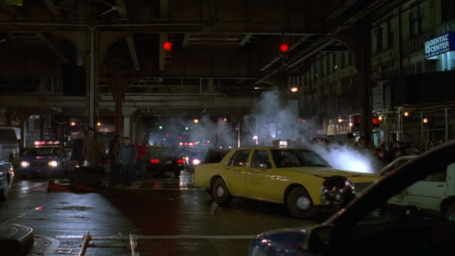 vídeos y material grabado en eventos de stock de medium angle of three or more new york city blue and white police cars converge under a section of elevated railway. see siren or lights flashing on police cars.  see yellow taxi cab. see pedestrians. camera pans up to elevated railway at end. - 1996