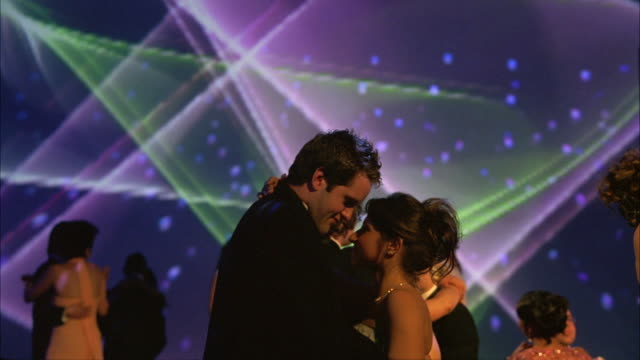 WIDE ANGLE OF HIGH SCHOOL STUDENTS OR COUPLES WEARING EVENING GOWNS AND TUXEDOS SLOW DANCING IN BALLROOM AT SCHOOL PROM, DANCE, PARTY OR CELEBRATION. SHAPES AND COLORS PROJECTED ON MOVIE SCREEN IN BG.