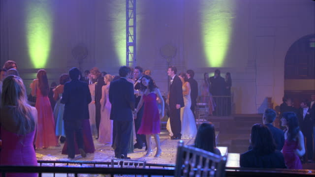 wide angle of teenagers, high school students or couples wearing evening gowns and tuxedos dancing on dance floor at school prom, dance, party or celebration. flashing lights. could be in hotel. - high school prom stock videos & royalty-free footage