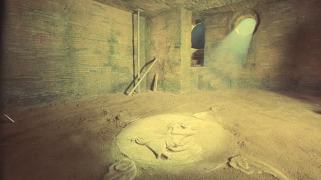 MEDIUM ANGLE OF CRYPT OR VAULT INSIDE BRICK BUILDING WITH ARCH DOORWAY, ROUND WINDOW. BRIGHT LIGHT SHINES FROM OUTSIDE, ILLUMINATES BAS-RELIEF STONE SCULPTURE DISC ON FLOOR. COULD BE TEMPLE CARVING.