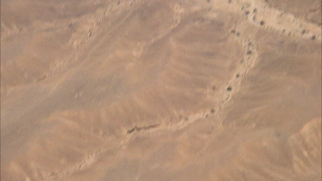 HIGH ANGLE DOWN TRACKING SHOT OF DOGFIGHT OF F-16 FIGHTER AND TWO KFIR JETS. ALL JETS EXIT TO BOTTOM RIGHT, DESERT ON GROUND. ACTION. MIDDLE EAST.