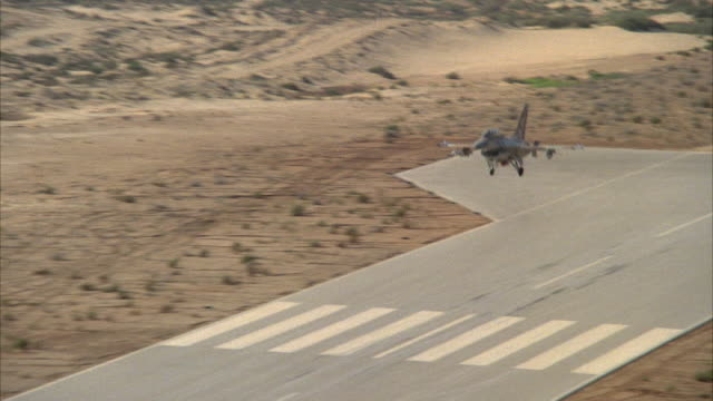 TRACKING SHOT OF A CAMOUFLAGE F-16 FIGHTER JET APPROACHING RUNWAY IN DESERT. SEE JET BEGIN TO TOUCH DOWN AS IT MOVES FURTHER DOWN RUNWAY.