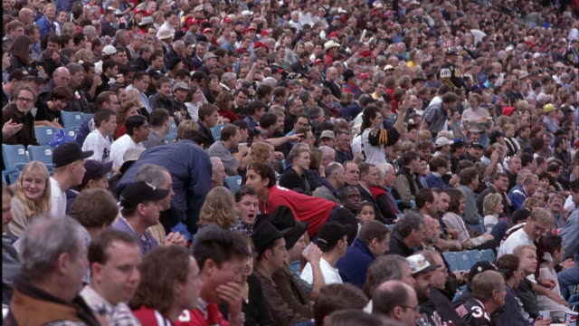wide angle of crowd at stadium. could be football, baseball, basketball, or hockey game at sports arena. see people watching, cheering, clapping, and talking. camera pans left and right. - baseball sport stock videos & royalty-free footage