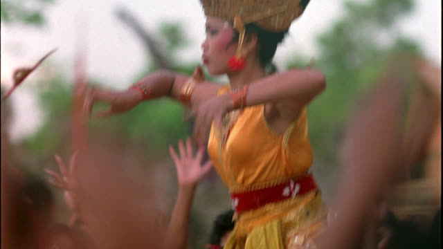 MEDIUM ANGLE OF DANCERS PERFORMING RITUAL DANCE OR CEREMONY, POSSIBLY BALIH-BALIHAN, JANGER, KEBYAR, LEGONG, OR KECAK DANCE.  SEE OUT OF FOCUS HEADS OF PEOPLE IN CROWD WATCHING DANCE, HANDS AND ARMS RAISED IN THE AIR.