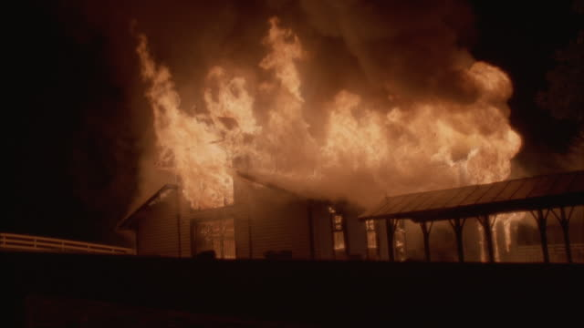 medium angle of burning horse stable or farm building. could be country church or community center. fire and flames consume building, heavy black smoke in top of frame. - barn点の映像素材/bロール